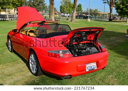 BAKERSFIELD, CA - OCTOBER 4, 2014: A red 2002 Porsche 911 Carrera convertible is looking pretty and ready for judging at the local Porsche club's  Concours D'Elegance.  - stock photo