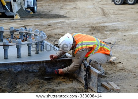 BAKERSFIELD, CA - OCTOBER 29, 2015: A workman strips forms away from a poured concrete foundation. Large anchor bolts will keep a column in place.