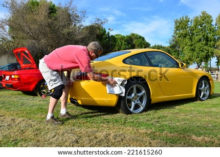 BAKERSFIELD, CA - OCTOBER 4, 2014: Dave Bratcher does some last minute polishing on his yellow Porsche 911 Carrera competing in the local Porsche club's  Concours D'Elegance.  - stock photo