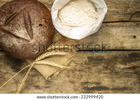 Bakery background. Rye bread with wheat ears and flour on wooden table - stock photo