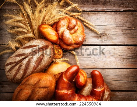 Bakery Bread on a Wooden Table. Various Bread and Sheaf of Wheat Ears over Wood Background - stock photo