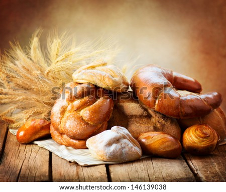 Bakery Bread on a Wooden Table. Various Bread and Sheaf of Wheat Ears Still-life.  - stock photo