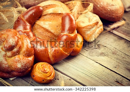 Bakery Bread on a Wooden Table. Various Bread and Sheaf of Wheat Ears Still-life