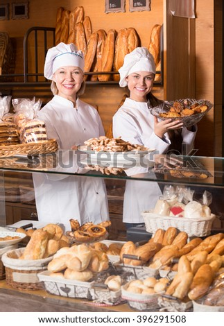 Bakery commerce staff offering bread and different pastry for sale - stock photo