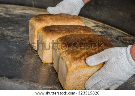 Bakery. Hands take baked bread - stock photo