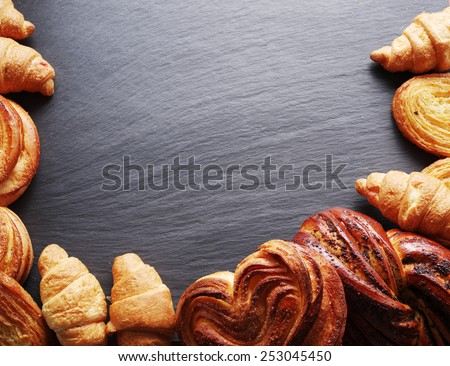Bakery products arranged as frame on grey board. - stock photo