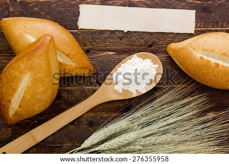 Bakery products flour in a wooden spoon and stalks of wheat. - stock photo