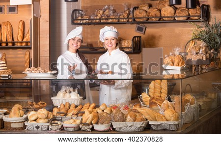 Bakery staff offering bread and different pastry for sale - stock photo