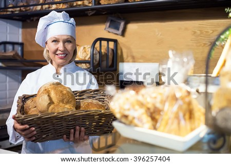 Bakery staff working in bakery with bread  - stock photo