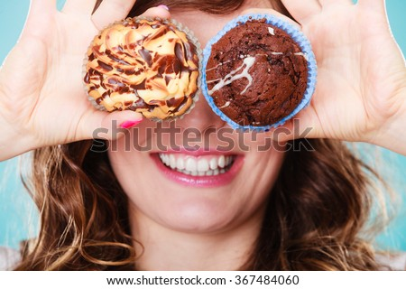 Bakery, sweet food and happiness concept. Closeup smiling woman having fun holding cakes in hands covering eyes with cupcakes - stock photo