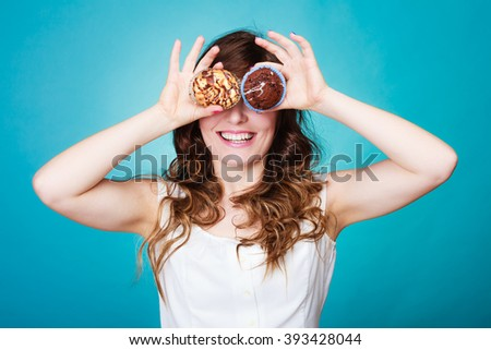 Bakery, sweet food and happiness concept. Closeup smiling woman having fun holding cakes in hands covering eyes with cupcakes blue background - stock photo