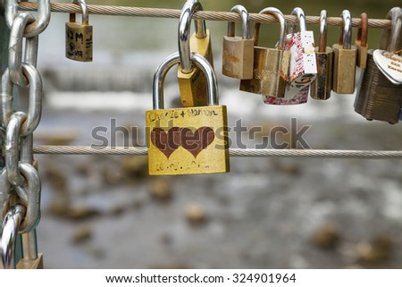 Bakewell, Derbyshire, England, UK - July 19, 2015: Love locks attached to the cable on weir bridge, Bakewell, Derbyshire, England, UK, - stock photo