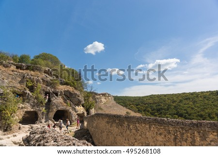 BAKHCHISARAY, REPUBLIC of CRIMEA, RUSSIA - SEPTEMBER 13.2016: Tourists are considering monastic cells in the rock. The medieval town-fortress Chufut-Kale