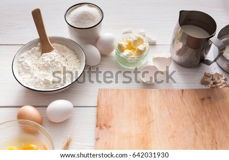 Baking background. Cooking ingredients for dough and pastry making and wooden pizza board on white rustic wood. Above view with copy space, mockup for menu, recipe or culinary classes.