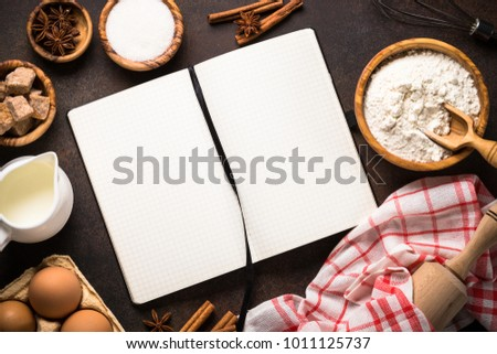 Baking background. Ingredients for cooking baking - flour, eggs, sugar, milk and spices with recipe book. Top view on dark stone table.