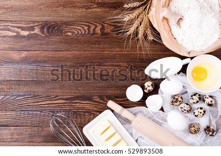 Baking background. Ingredients for cooking. Flour in paper bag, eggs, butter, kitchen utensils on wooden background. Copy space. Top view