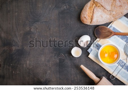 Baking background with blank cook book, eggshell, bread, flour, rolling pin. Vintage wood table from above. Rustic background with free text space. - stock photo