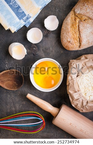 Baking background with bread, eggshell, flour, rolling pin - stock photo