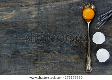 Baking background with egg yolk in vintage spoon and eggshell over dark wooden texture. Top view. - stock photo