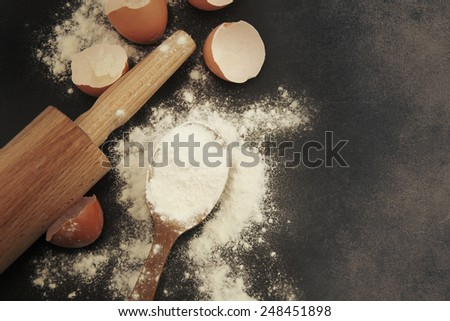 Baking background with eggshell and rolling pin - stock photo
