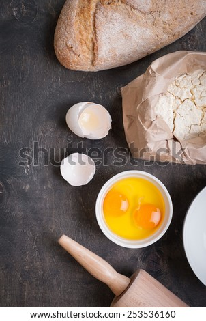 Baking background with eggshell, bread, flour, rolling pin. Close up - stock photo