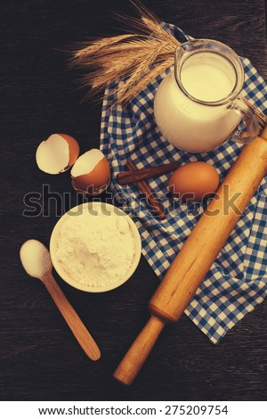 baking background with eggshell, milk, wheat and rolling pin - stock photo