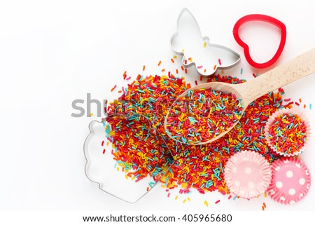 Baking background with ingredients: colorful sugar sprinkling, cutter for cookies, mold for cake isolated on white background empty space for text top view - stock photo