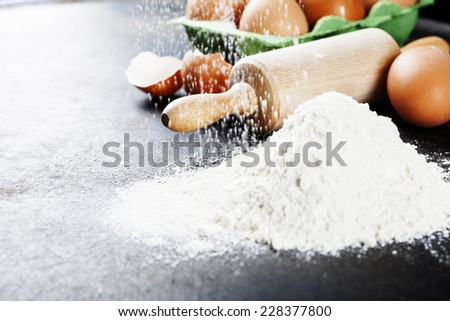 baking background with raw eggs, rolling pin and flour - stock photo