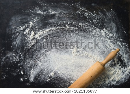 Baking background with the rolling pin and flour. On the dark table. Copy space for text. Top view
