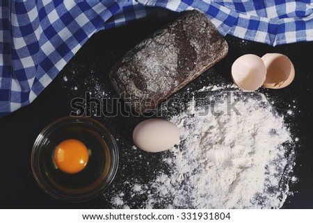 Baking, baking bread. Products. Crumble flour, eggs and a loaf of bread. Black bread. Culinary skills. Low key. Tablecloth in a cage. The blue-and-white checkered cloth. - stock photo