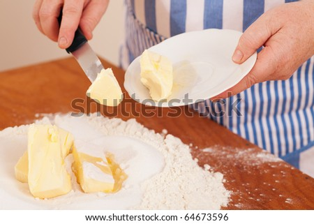 Baking biscuits, woman putting butter in the flour