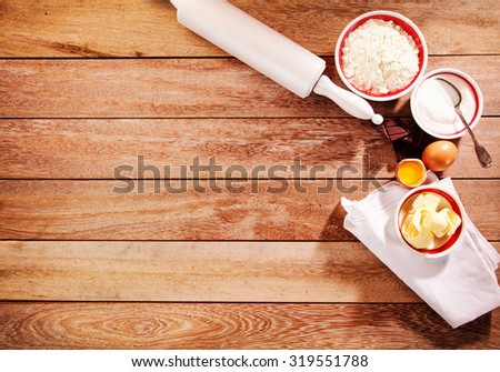 Baking border with a wooden rolling pin and fresh ingredients in bowls laid out ready on a rustic wood table with copyspace, overhead view - stock photo