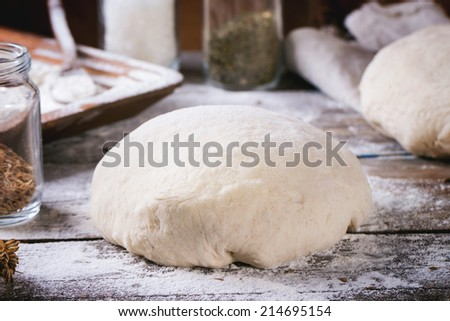 Baking bread. Dough on wooden table with flour, rolling-pin and jars with backing ingredients.