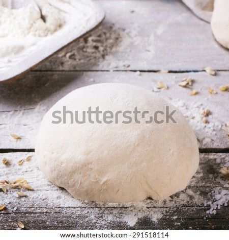 Baking bread. Dough on wooden table with flour, rolling-pin and jars with backing ingredients. Square image with selective focus