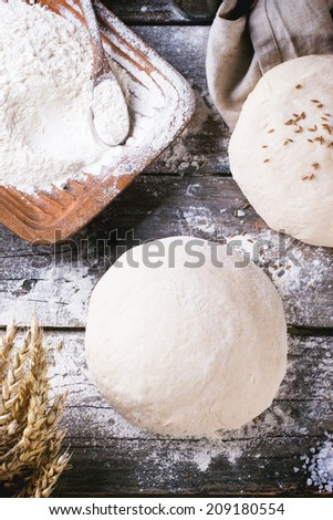 Baking bread. Dough on wooden table with flour, rolling-pin and jars with backing ingredients. Top view - stock photo