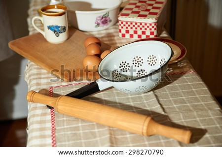 Baking cake in rural kitchen - dough recipe ingredients eggs, flour, butter, sugar and rolling pin on vintage wood table from above