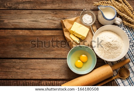 Baking cake in rural kitchen - dough recipe ingredients (eggs, flour, milk, butter, sugar) and rolling pin on vintage wood table from above. Rustic background with free text space. - stock photo