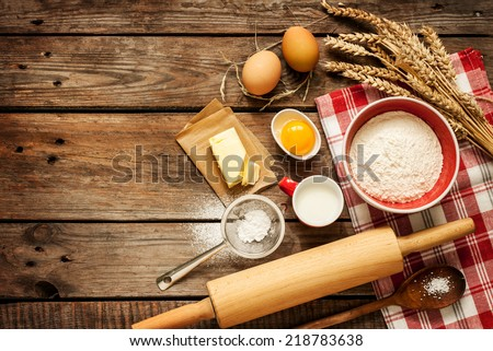 Baking cake in rural kitchen - dough recipe ingredients (eggs, flour, milk, butter, sugar) on vintage wooden table from above. Background layout with free text space. - stock photo