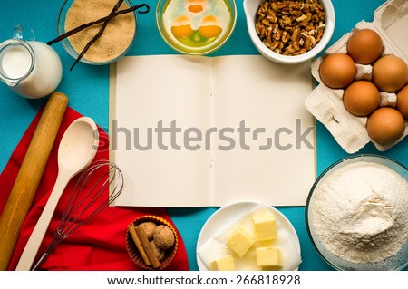 Baking cake in rural kitchen - dough recipe ingredients (eggs, flour, milk, butter, sugar) with walnuts, vanilla. Recipe book in the center. - stock photo
