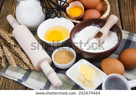 Baking cake in rural kitchen - dough recipe ingredients (eggs, flour, sugar) on a wooden table - stock photo