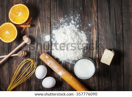 Baking cake in rural kitchen - dough recipe ingredients on vintage wooden table from above - stock photo