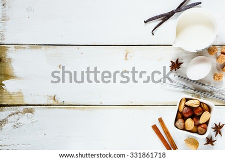 Baking cake on white wooden table from above - dough recipe ingredients (egg, milk, sugar, nuts, vanilla and cinnamon sticks). Background with free text space. - stock photo