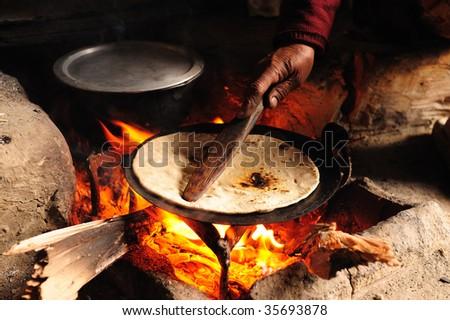 Baking Chapati on Wood Fire - stock photo