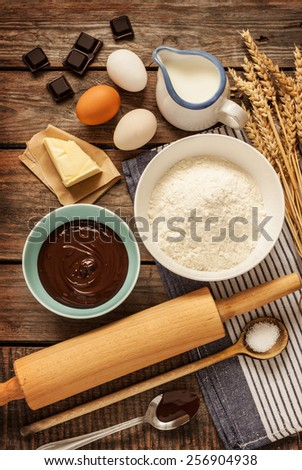 Baking chocolate cake in rural or rustic kitchen. Dough recipe ingredients (eggs, flour, milk, butter, sugar) on vintage wood table from above. - stock photo
