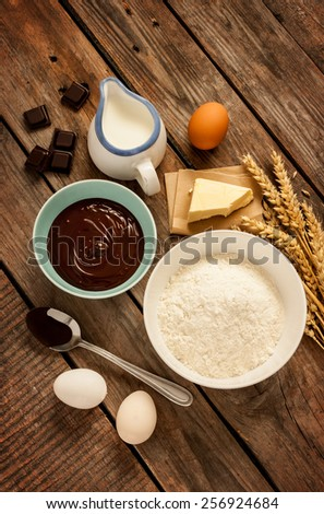 Baking chocolate cake in rural or rustic kitchen. Dough recipe ingredients (eggs, flour, milk, butter) on vintage wood table from above. - stock photo