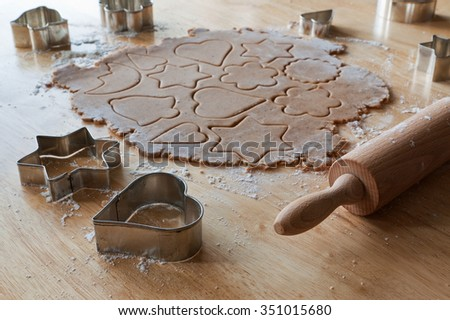 Baking christmas gingerbread cookies. Gingerbread dough, christmas cookie cutters and rolling pin on kitchen table. - stock photo