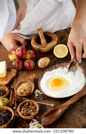Baking concept background. Baker with ingredients for pastry desserts. Apples, lemon, sugar, walnuts - stock photo