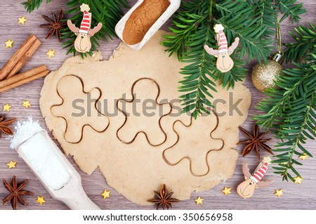 Baking cookies. Dough, gingerbread men, flour, cinnamon, anise, Christmas tree and ornaments on the wooden background. Ingredients for Christmas baking. - stock photo