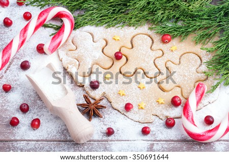 Baking cookies. Dough, gingerbread men, flour, cinnamon, anise, cranberries, cinnamon, Christmas canes on wooden background. Ingredients for Christmas baking. Close up - stock photo
