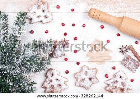 Baking cookies. Flour, chocolate, cranberries, cinnamon, anise, rolling pin on a wooden background. Christmas card. Top view - stock photo